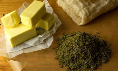 A cutting board holds butter, cheese cloth, and a pile of shake, someone is preparing to make homemade canna-oil and canna-butter.