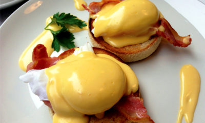 Two poached eggs sit atop toasted English muffins and topped with a Lemon Haze hollandaise sauce.