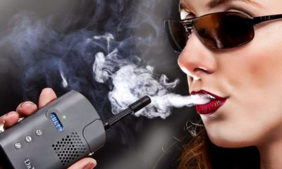 A brunette woman with sunglasses and red lips blows smoke from a Da Vinci Vaporizer