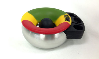 A rasta colored Ash Cache tray on a white table.