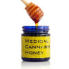 A jar of medical cannabis honey is pulled out by a dipper.