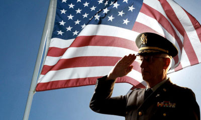 An veteran dressed in uniform salutes while standing in front of a flag.