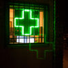 Buds and Roses, a premier dispensary in So Cal, is closed for the day as a green medical cross shines through barred windows.