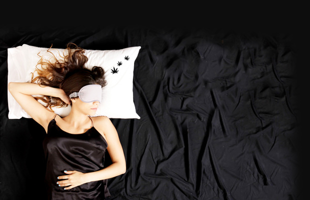 A woman rests peacefully on black silken sheets and rests her head on a white pillow ebroidered with little black pot leaves.