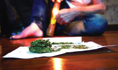 Man Sits On Floor with Bong and Marijuana