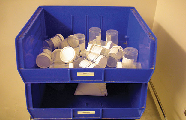 Urine Collection Bottles Sit Empty in a Blue Receptical