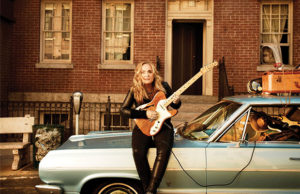 Melissa Etheridge Sits Atop Her Car Playing A Guitar in Front of a Brick Building