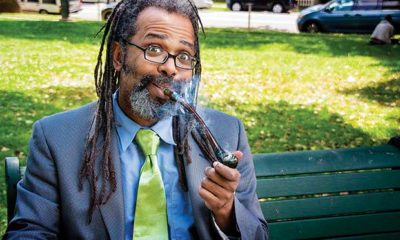 Ngaio Bealum puffs on a pipe while wearing a blue suit and green tie on a park bench as he answers Dear Dabby questions.