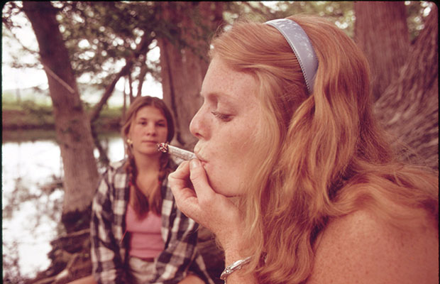 A 3x5 image of a woman in the 60s puffing on a joint while her friend watches on in conservative Texas.