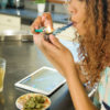A woman takes a hit from a shell pipe, on the counter around her there is a glass of juice, tablet, and a dish of beautiful buds.